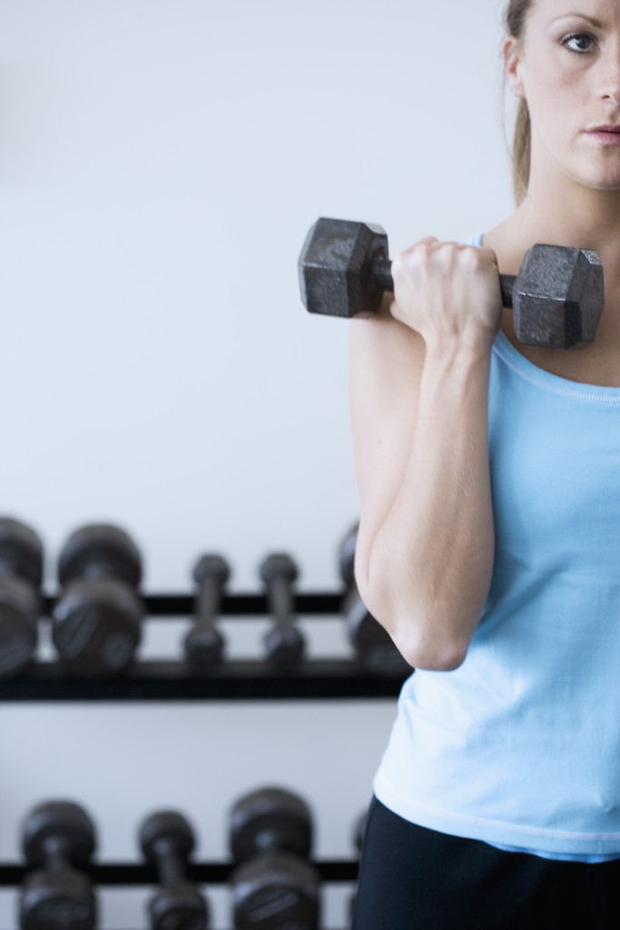 Woman Curling Dumbbells --- Image by © Royalty-Free/Corbis