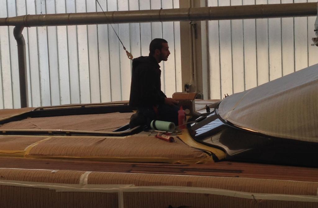Håndværker i gang med at lakere en båd