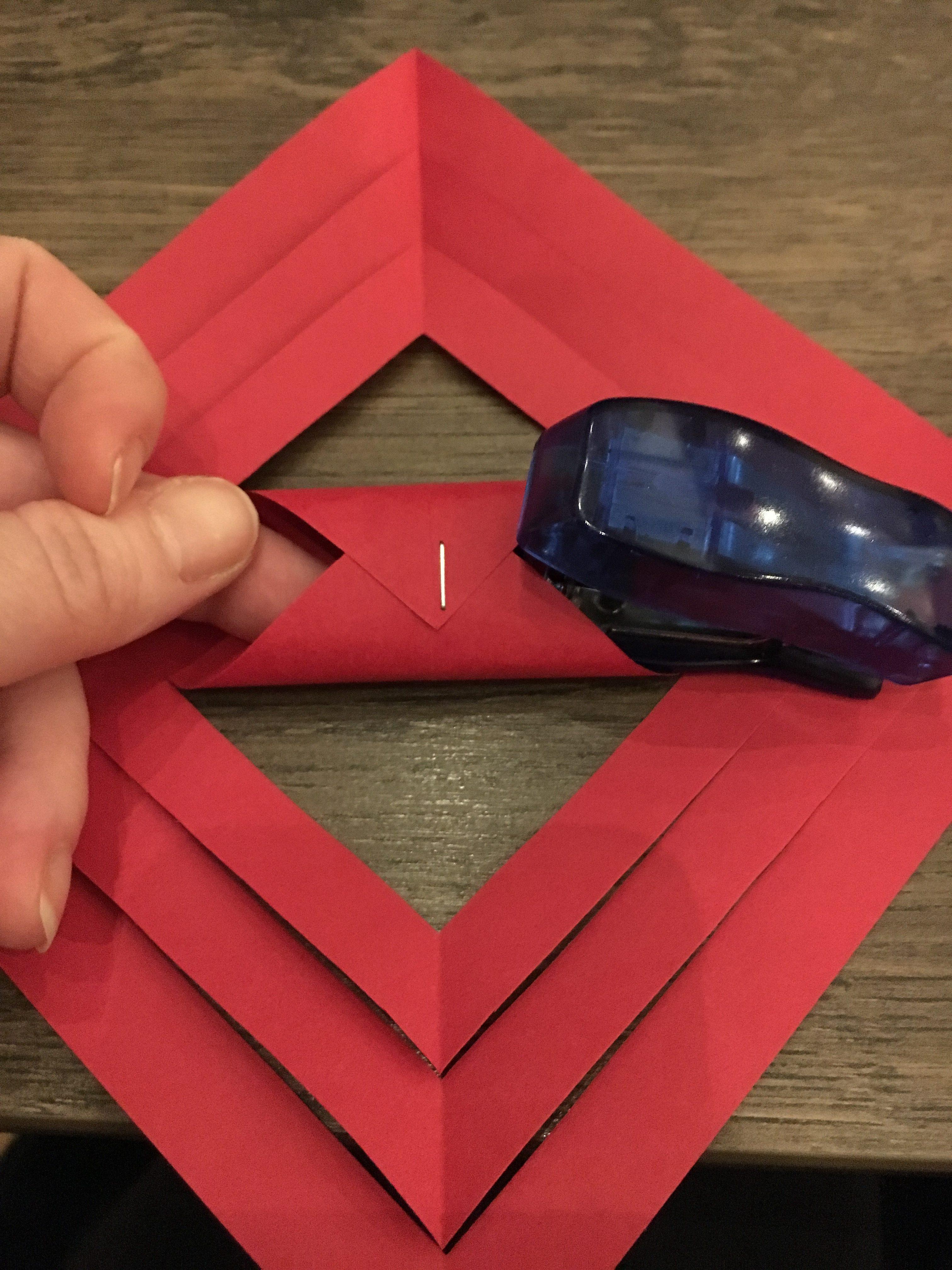 så folder du de 2 inderste spidser oven på hinanden og hæfter dem sammen