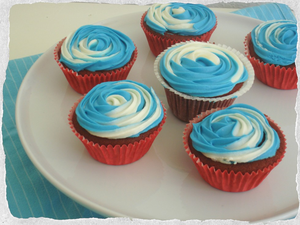 Homemade red velvet cupcakes with blue and white frosting