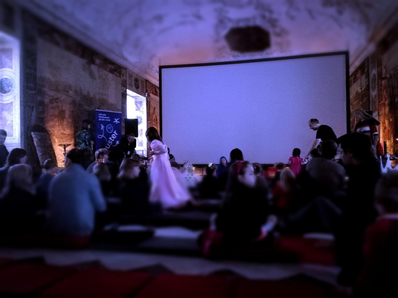Prinser og prinsesser gør sig klar til Tornerose på storskærmen i den eventyrlige riddersal