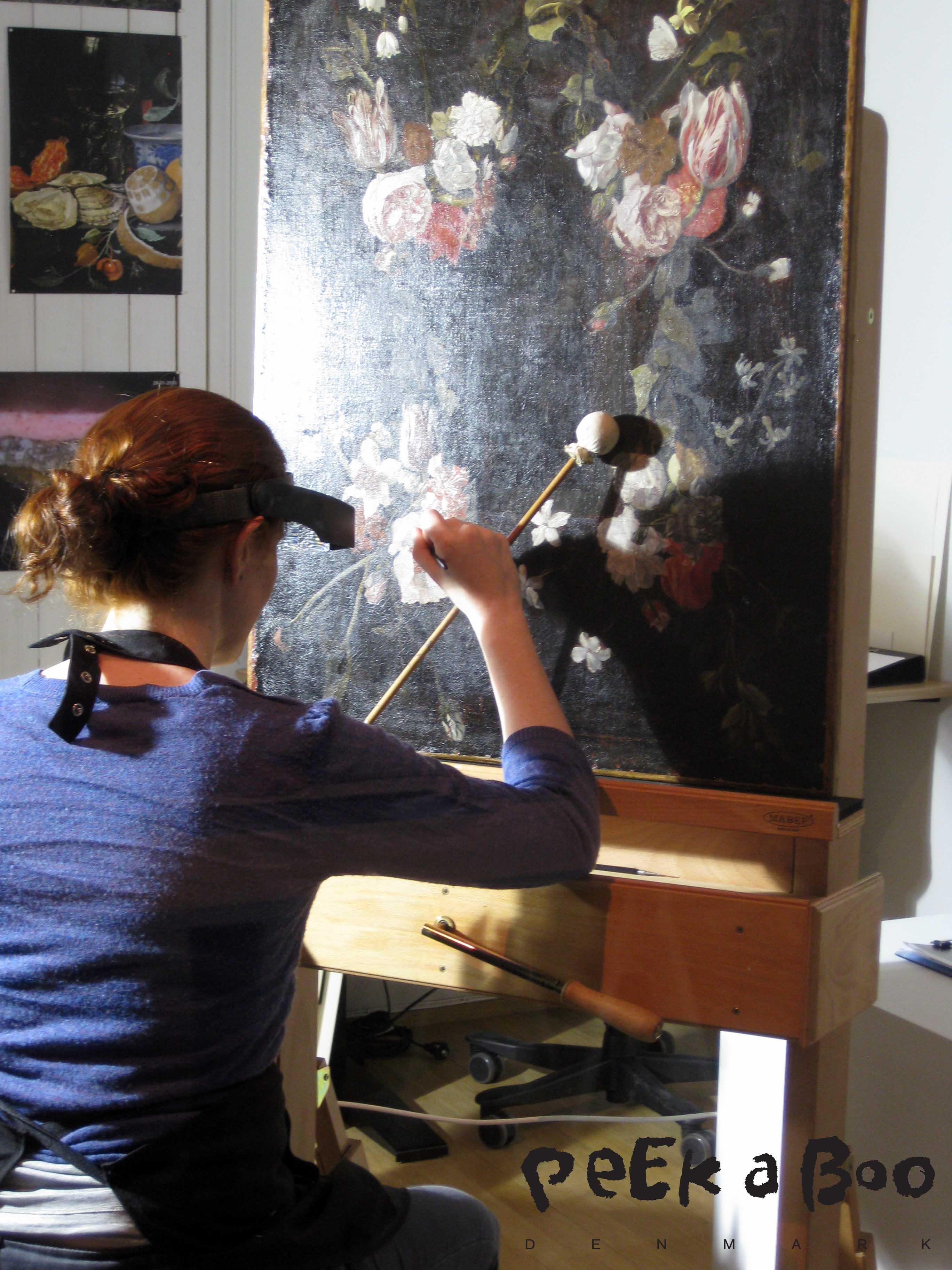 Konservator igang med restaureringen af et af de gamle malerier