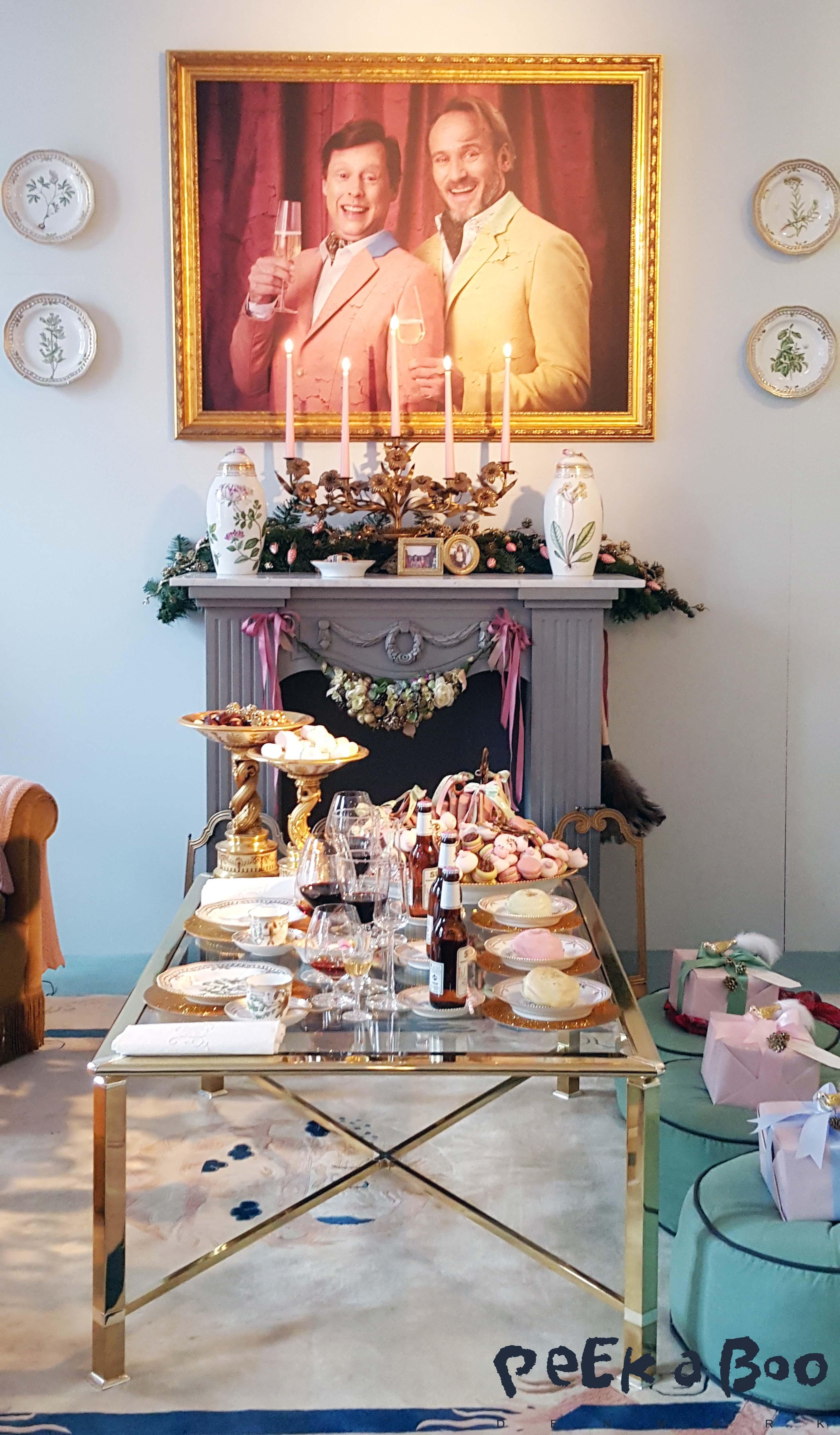 Snobberne Fritz og Poul's stue, hvor der er dækket op i deres foretrukne pastelfarver, og der er kinesiske øl til de tre aupair piger og i dagens anledning også sugerør. De lyserøde macaroes er formet som bryster, og juletræet er overdænget med med glimmer. Bag dette står skuespillerne Rasmus Botoft og Martin Buch.