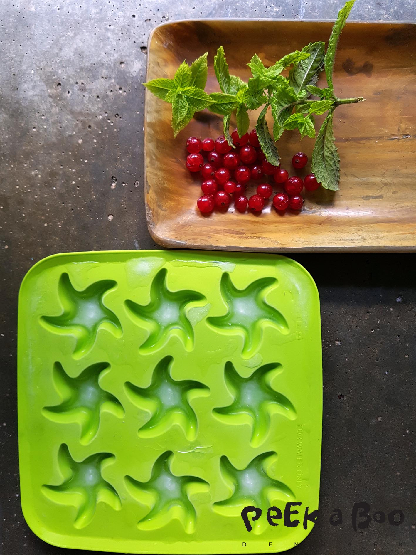 Freeze the botom of the icecubes. Use small berries and mint leaves.