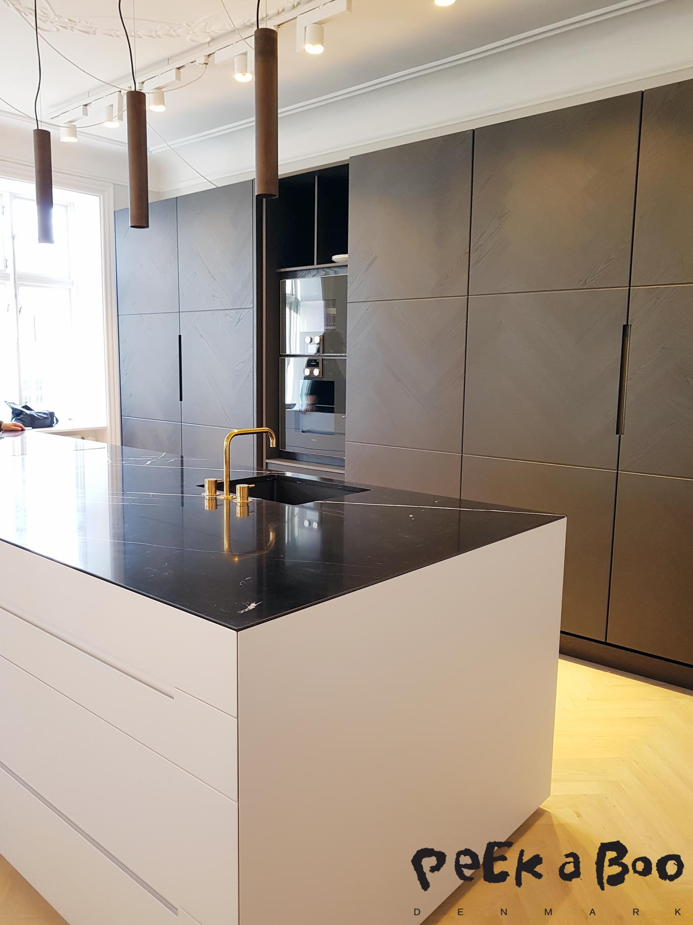The closed kitchen with the dark wood and black Italian marble.