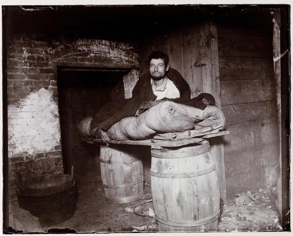 A man atop a make-shift bed that consists of a plank across two barrels.