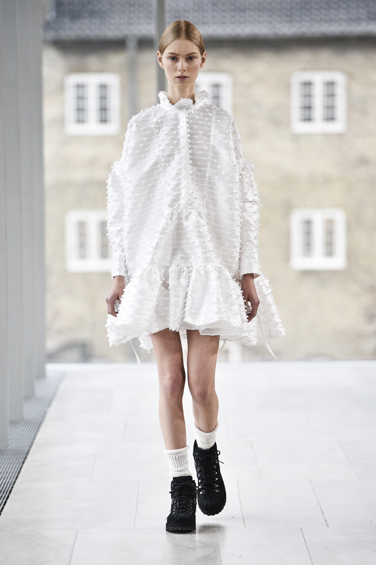 Smuk og enkel A shaped kjole i en fin let skinnende metervare med broderi på og bred flæse forneden.