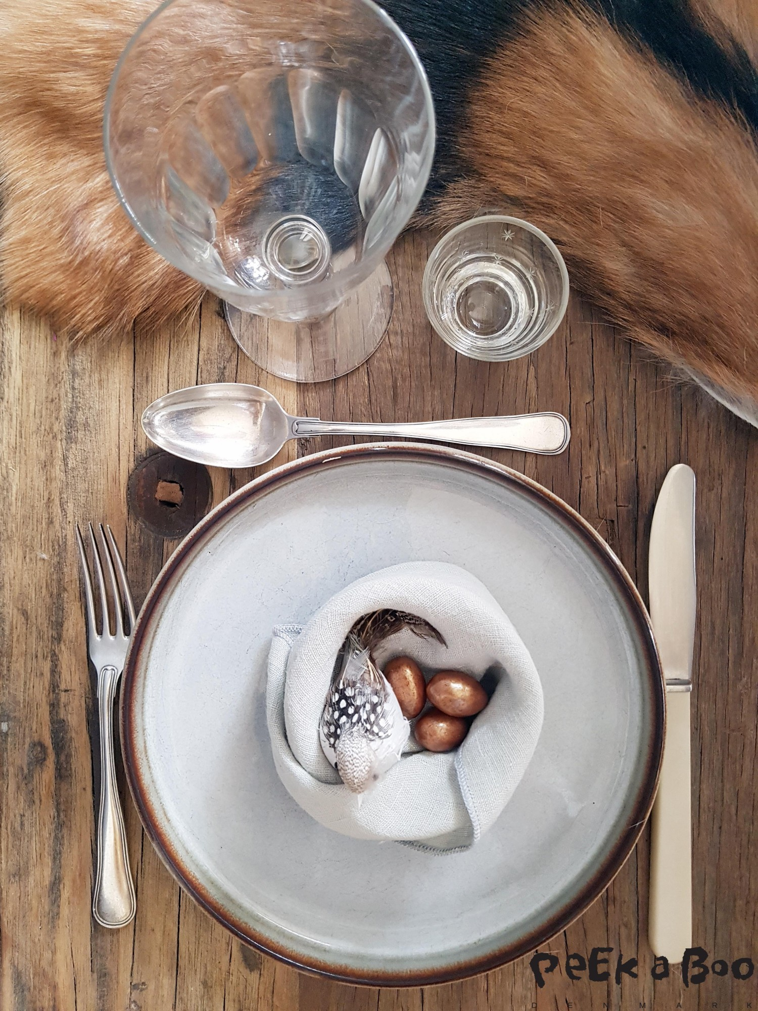 Nordic simplicity on your Easter table. The raw table is actually a bench from Ib Laursen, and the stoneware is secondhand but called Sonja from Søholm. The cutlery is also found on a fleahmarket and so is the glasses. But the goat skin is from Jysk.