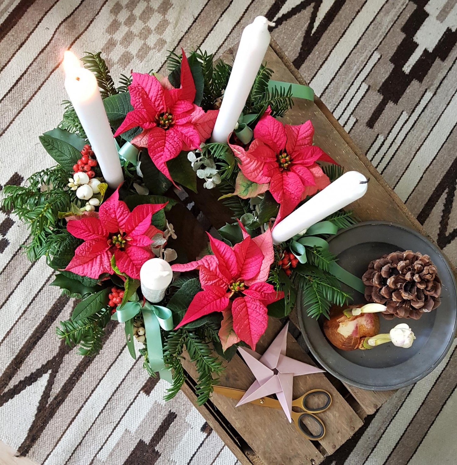 The advent wreath seen from above. The dark pink poinsettia is giving the wreath a colourful twist.
