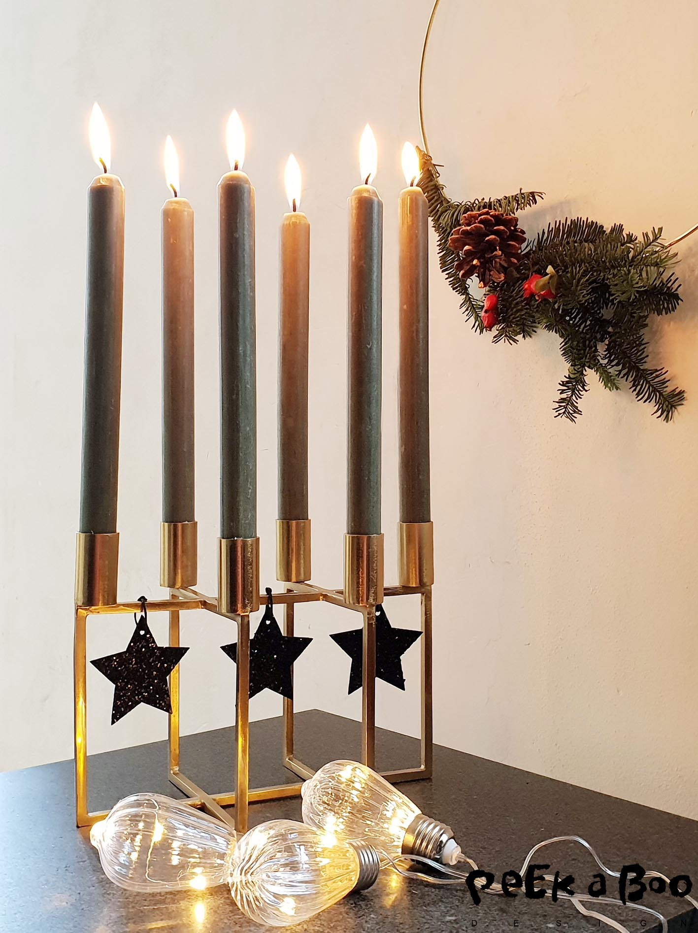 The simpel and elegant styling of a brass candleholder with some black glittering starts makes a modern christmas look.