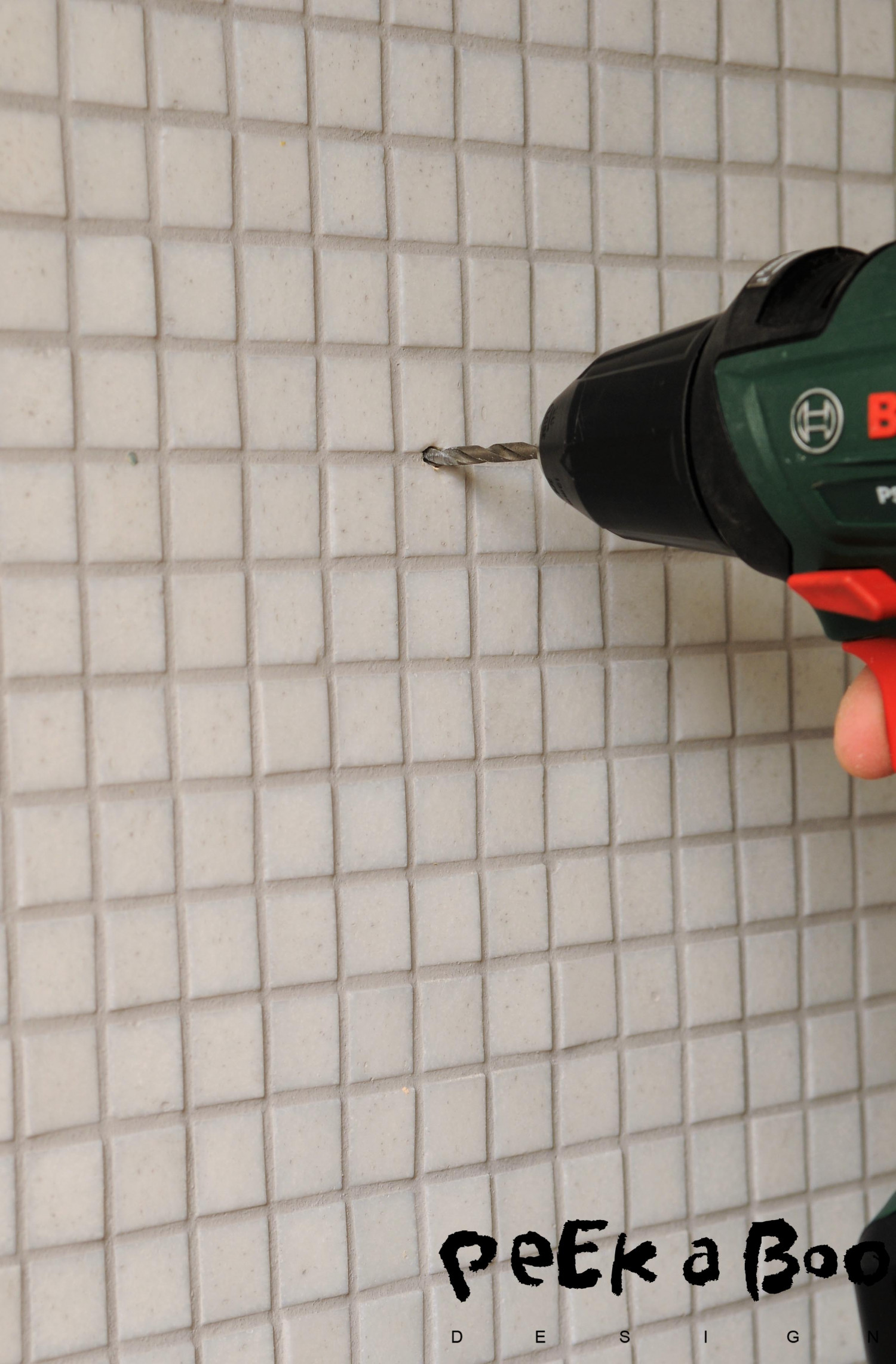 Drill a hole in the wall, try to make the holes between the glass mosaics.
