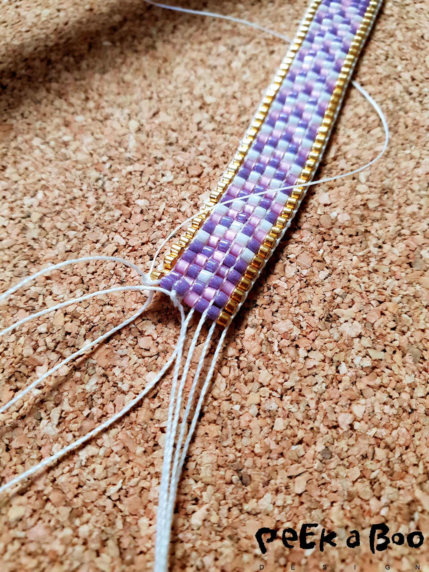 Now you also loosen the other end of the threads from the crossbar. And now tie the threads of the loom together two and two. so you close the weaving.