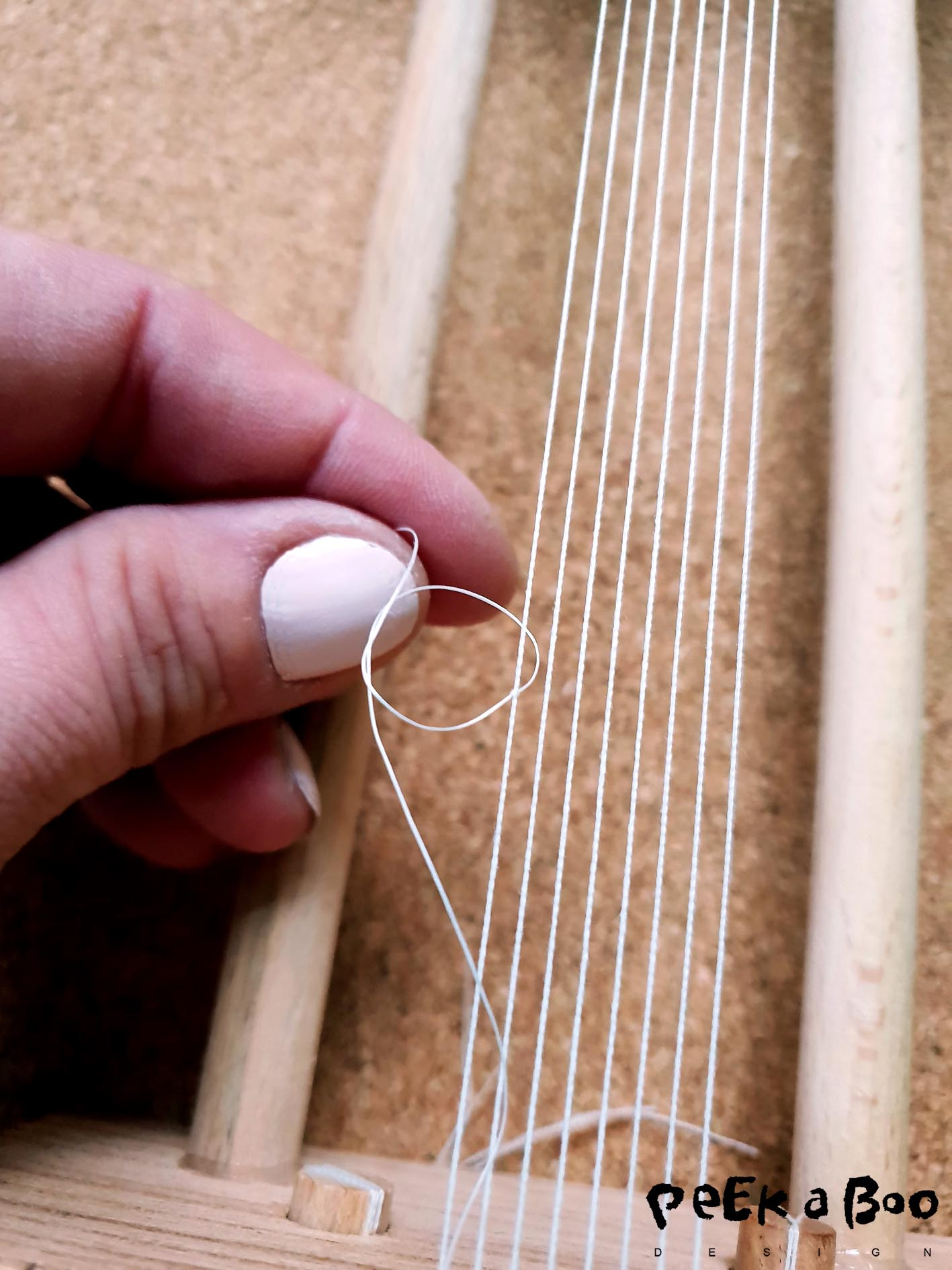 Thread your split needle with a long thread. I have made my approx. 2 m. It must now be attached to your outer left thread on the loom. Tie a double knot.