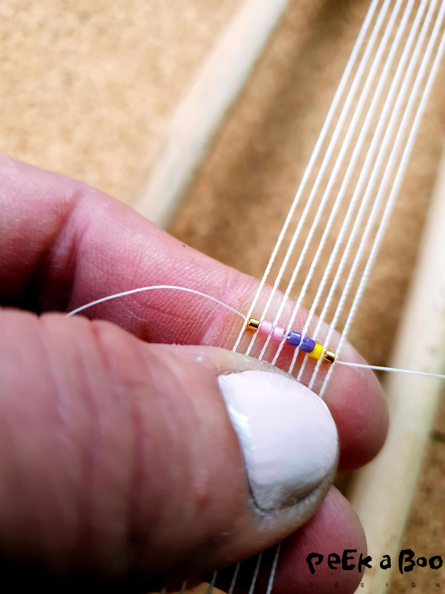 Put your first row of beads on your needle, hold them underneath the threads on the loom. So there is one pearl between each thread. Hold them against the threads with one finger. Then pull the thread and needle through