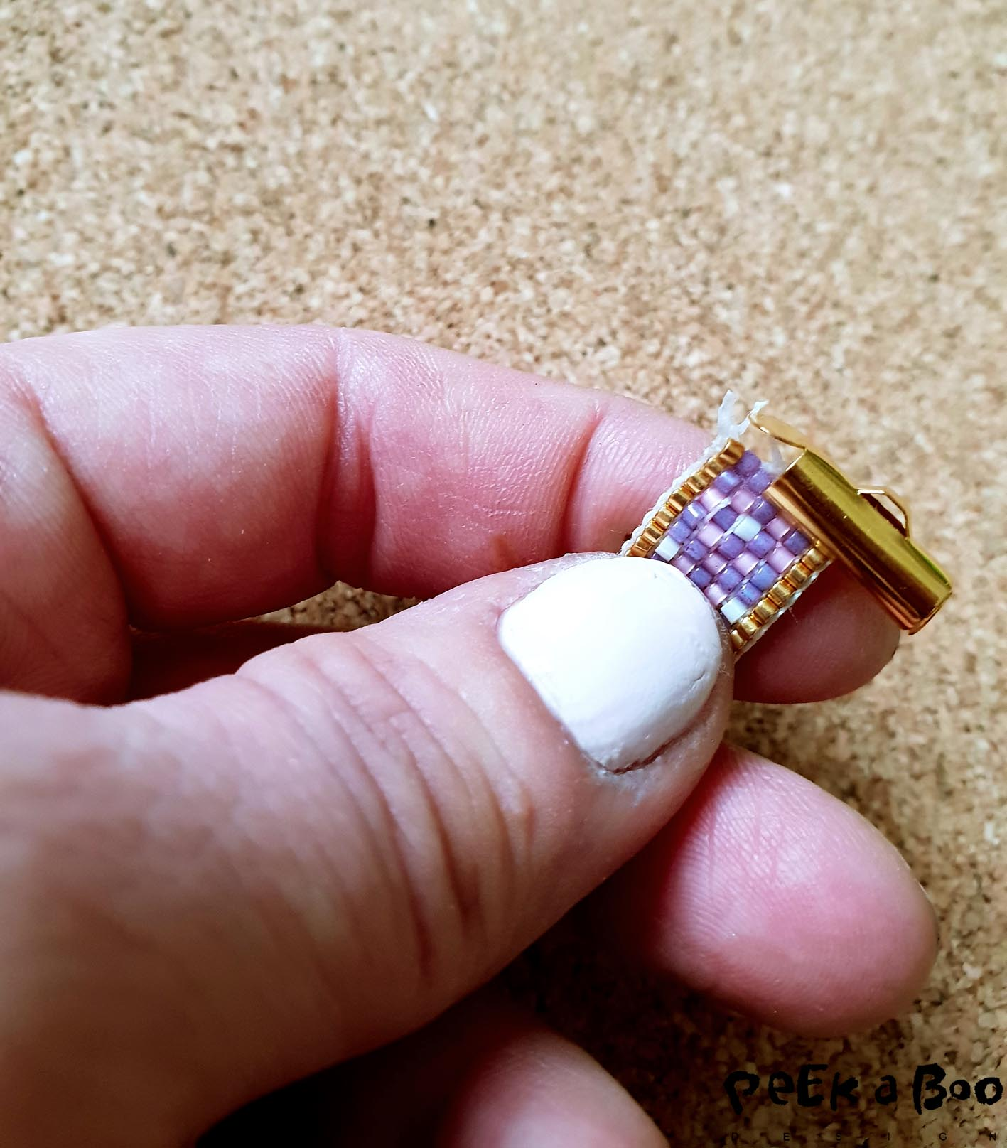 Now the end pieces must be fitted to the ends of the bracelet. The open end is driven over the last row of beads. And at the other end, drive an end piece over the first row of beads.