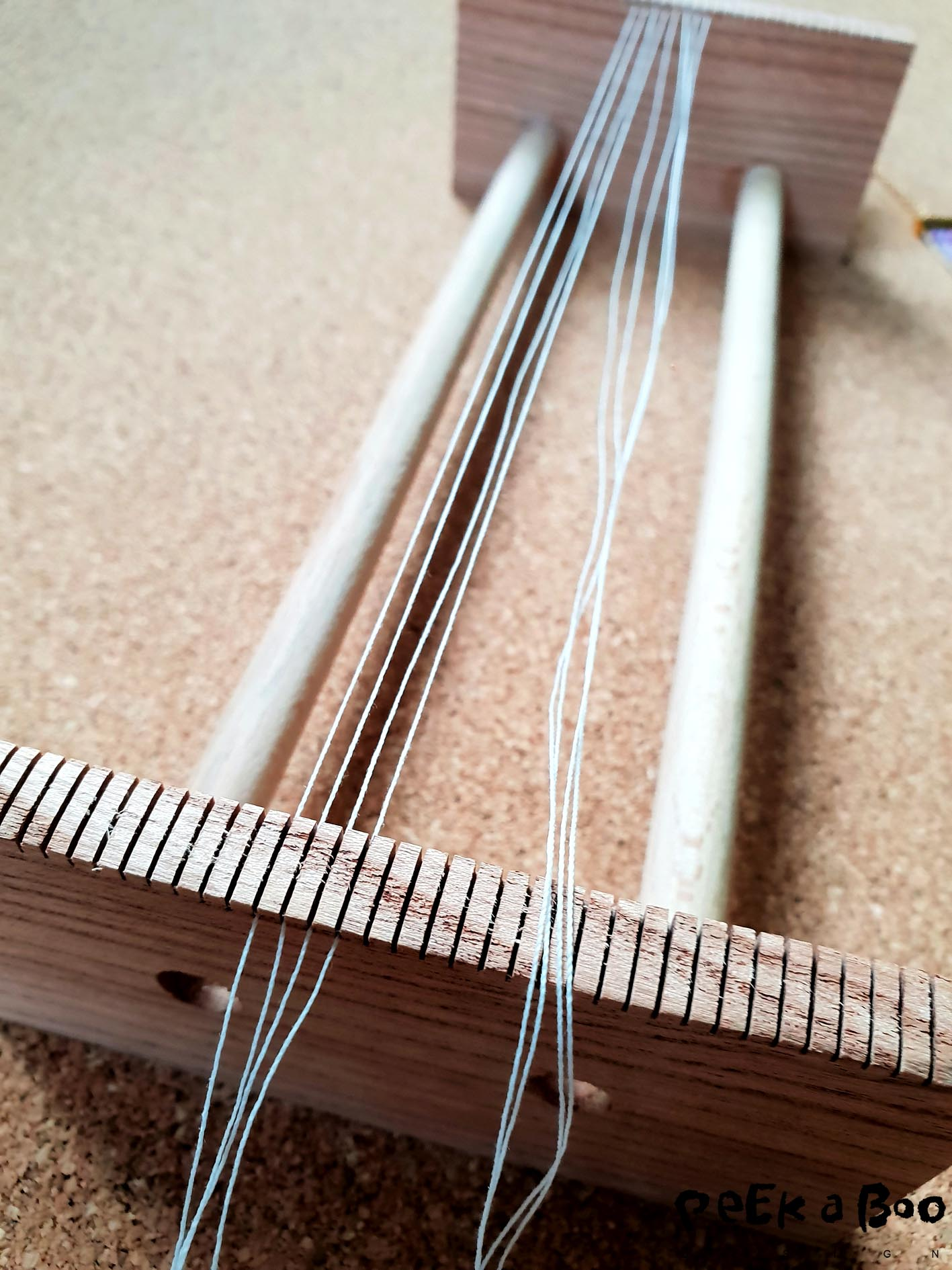 Start by threading your weave, you do that by cutting eight pieces of bead wire on each 55 cm. Tie them around the crossbar at one end.