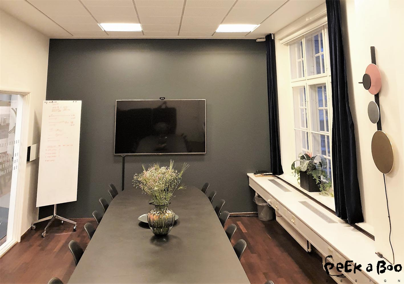 At the end wall of the big meetingroom there is a dark grey wall to keep a serious and calm atmosphere. I have added some textiles in form of velvet curtains from Jotex to get a cozy feeling to the room, aswell as the flowers does.