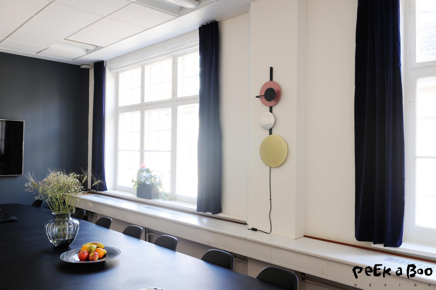 in the meetingroom there is only the pink spot on the wall lighthing from Please wait to be seated. And the wall is painted a dark grey to create a calm feeling. And to make the room more cozy I added velvet curtains in a blue colour from Jotex.