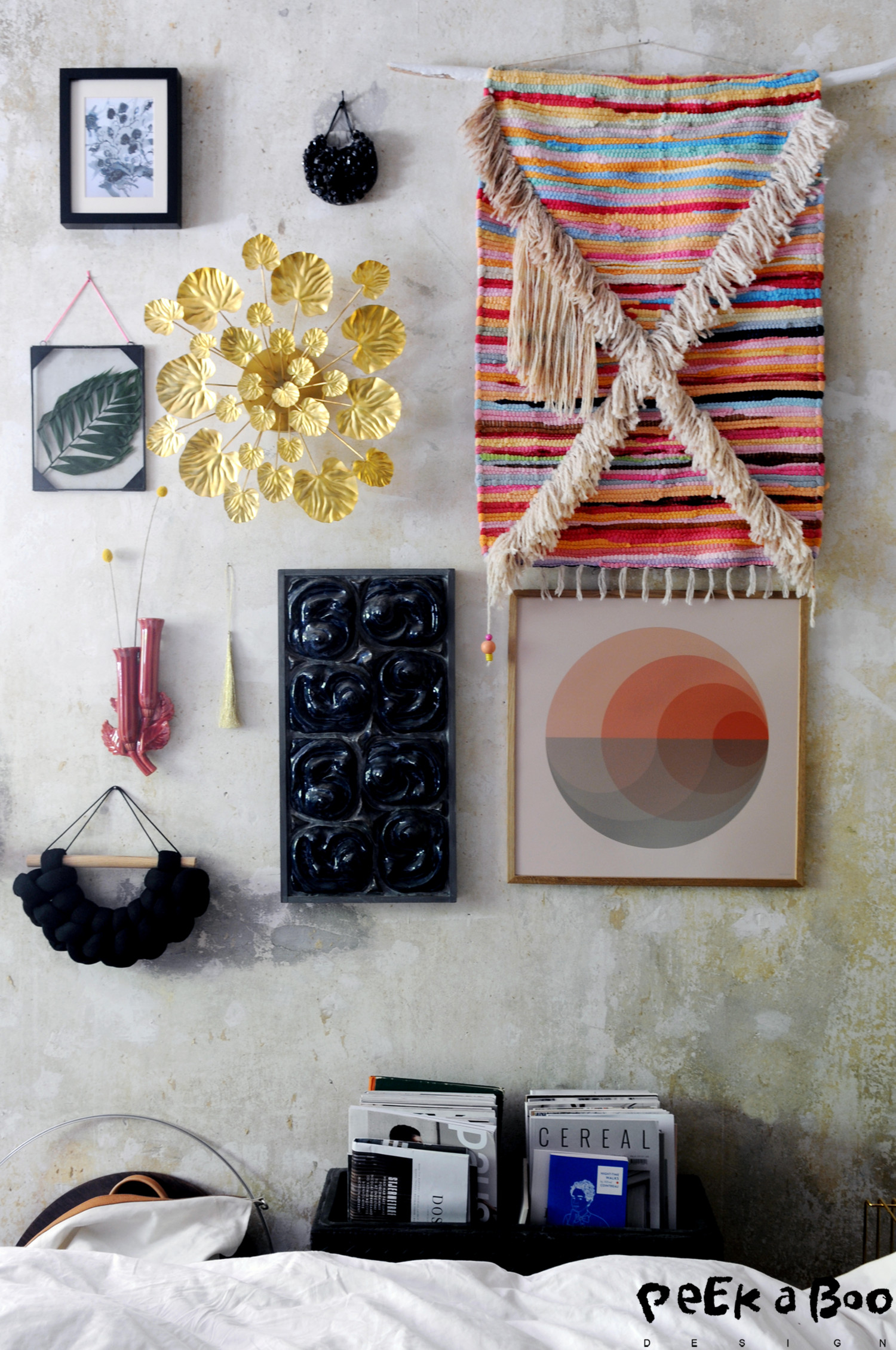 My gallerywall in the bedroom. From top left a small watercolor painting by Louise Dorph, next to that a small round ceramic artwork by Klejn & Strup, the textile wallhanger is made by me long time ago under that there is the poster Gradient by Vissevasse beside that to the right you see a blueish ceramic wallhanger, this is found secondhand and I have no clue who the artist is. And beside that there is a gold tassel, just because I like it. And beside that a vintage flowervase in art nouveau look this is a fleamarket find and below that you see a textile wallhanger from Klejn & Strup. The metal frame with double layer of glass is from Ib Laursen and I added the palm leaf myself, and in the middle you see the beautiful golden metal flower from Eden Outcast.