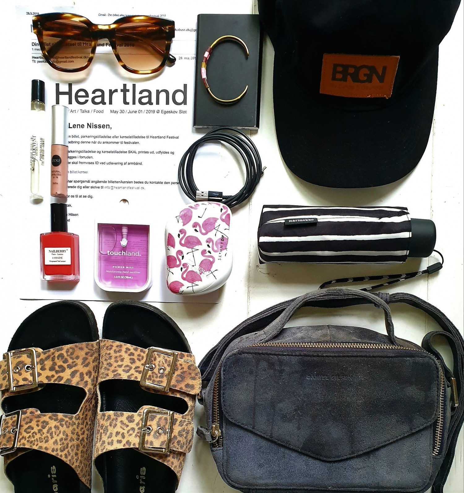 Festival essentials. Sunglasses from Jamie Looks, Bracelet from Useseme, cap from BRGN, perfume from Le Couvent Porto Bello, Lipgloss from Zenz organics, nailpolish from Nailberry, hand santizer, hairbrush tangleteaser, umbrella marimekko, slippers from Tamaris and cross-over suede bag from Daniel Silfen