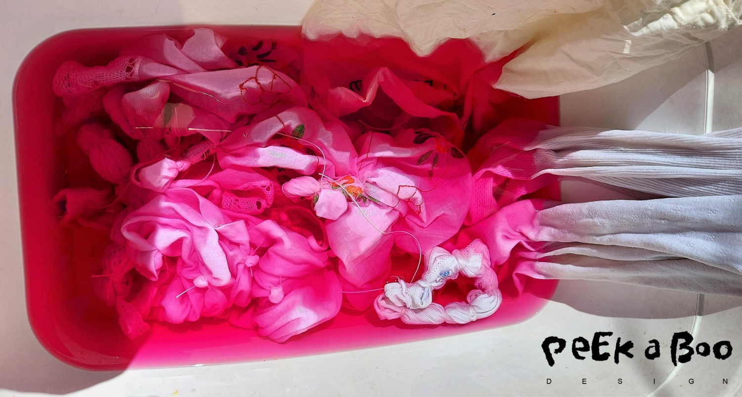 The garments in the pink colordye. You can see how I have tied string around the fabric to get the tie-dye effect.