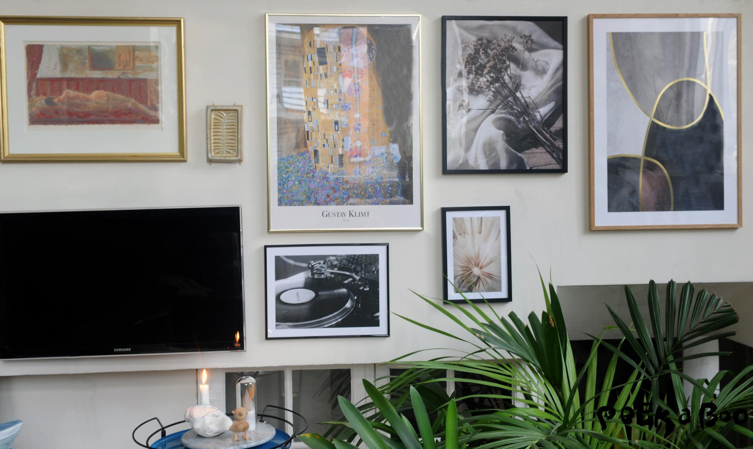 """I have tried to combine the graphic look with the black and white photos with some of my favorite art pieces as the Gustav Klimt """"the kiss"""" All of them together with a ceramic wallpiece, the TV and an art litography."""