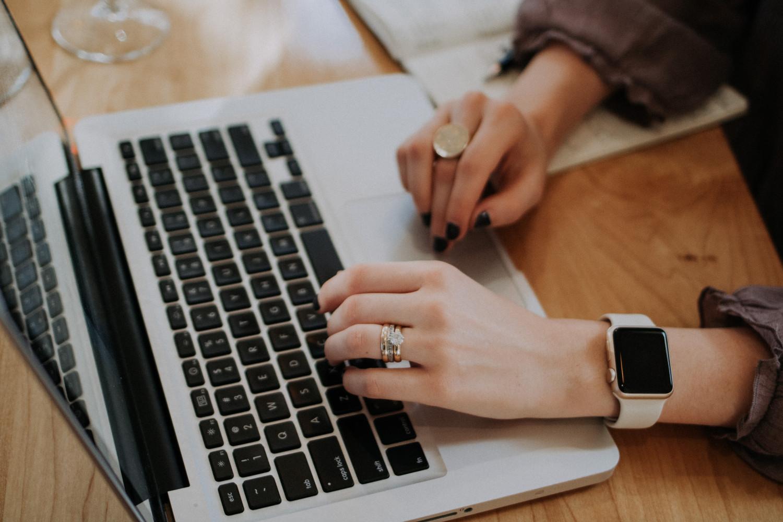 Billede af kvinde hænder ved en MacBook.