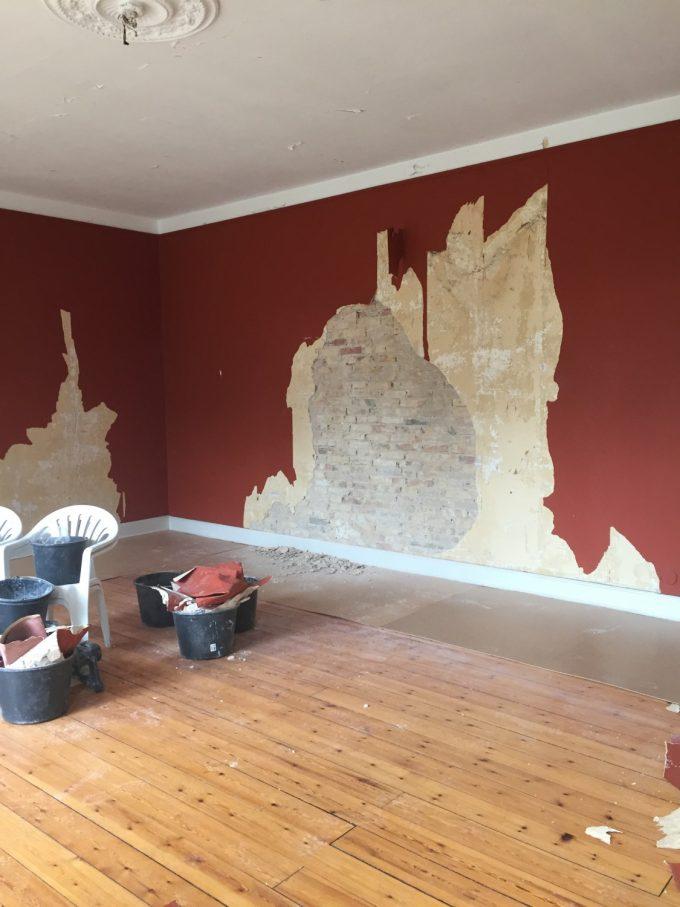 Tapeten var så løs på denne væg, så vi kunne skimte murstene inde bag ved. Så det tog ikke mange minutter at få rykket dette areal af.