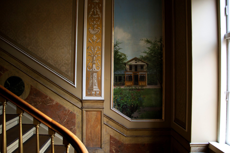 Opgangen til lejligheden, med maleri af familiens sommerhus. Al den flotte marmor er malet på- ikke for at hoppe over hvor gærdet var lavest, men fordi det ganske enkelt var dyrere at få en kunstner til at dekorere væggen, frem for købe ægte marmor. Der var med andre ord mere prestige i at få det malet.