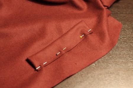 Det aflange stykke uld er her blevet bøjet på den aflange side, syet i begge ender og vendt med vrangen indad og ret udad. Til sidst er den sat fast på kanten af stoffet til sidesømmen (her dog lidt inde på stoffet, da noget af stoffet skal klippes af).