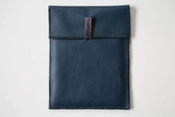 iPad-holder/etui i lukket format. Simpel, men med en sjov detalje med den alternative lukning og den orange snip.