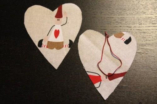 Fold snoren med knuderne i hver ende. Snoren placeres mellem de to stykker stof, der ligger med forsiderne mod hinanden. Knuderne skal stikke lidt ud af hjertet, også når man syer dem på symaskinen.
