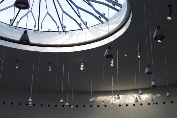 Lysindfaldet fra et stort, rundt loftsvindue. Det spaltede lys fra gitteret i vinduet dannede nogle sjove former ned på væggene.