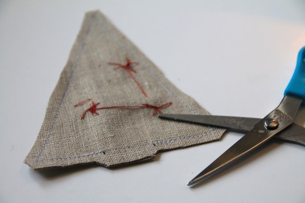 """Efter at have syet på symaskinen, klipper man kanterne """"rene"""", ca. ½ cm fra kanten, samt klipper hjørnerne af. Ved de 2,5 cm i bunden lader man dog ca. 1 cm være."""