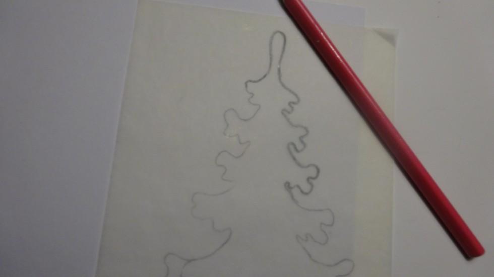 Juletræet tegnes over på et stykke hvidt pap.