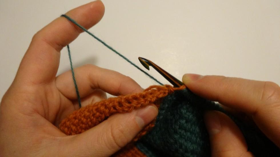 Den orange tråd (som der lige er hakket en række med) lægges til side og den nye farve tages frem fra forrige række. Det vil nok heller ikke gøre noget, hvis den orange farve blev lagt på den modsatte side af den nye tråd.