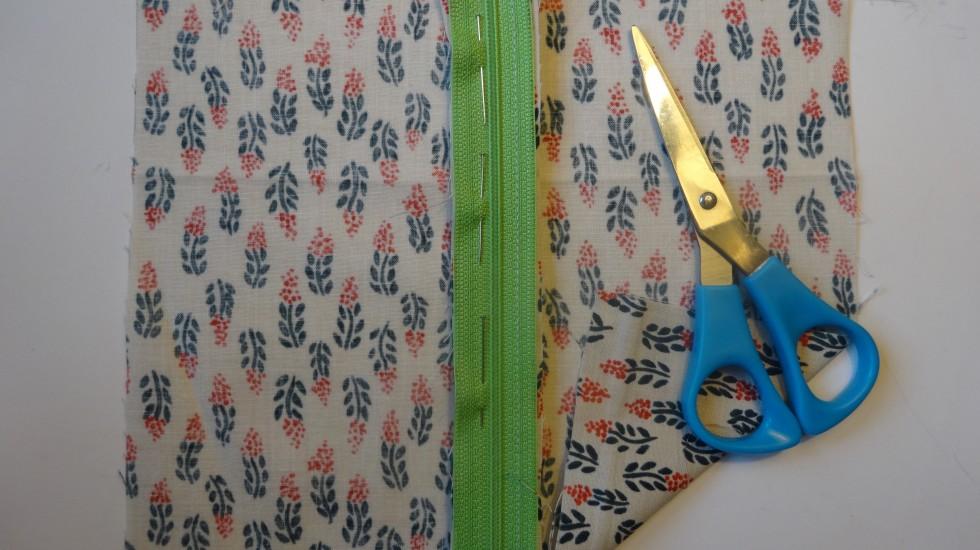 Stoffet sættes fast på lynlåsen med nåle. Vrangsiden af lynlåsen hæftes mod retsiden af stoffet.