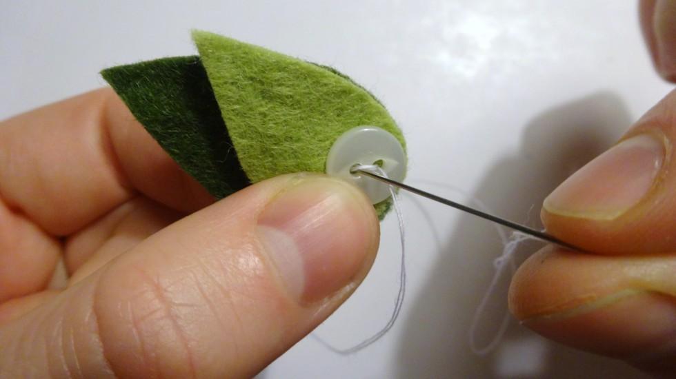 Nålen skal igennem de to lag filt og knappen på en gang.