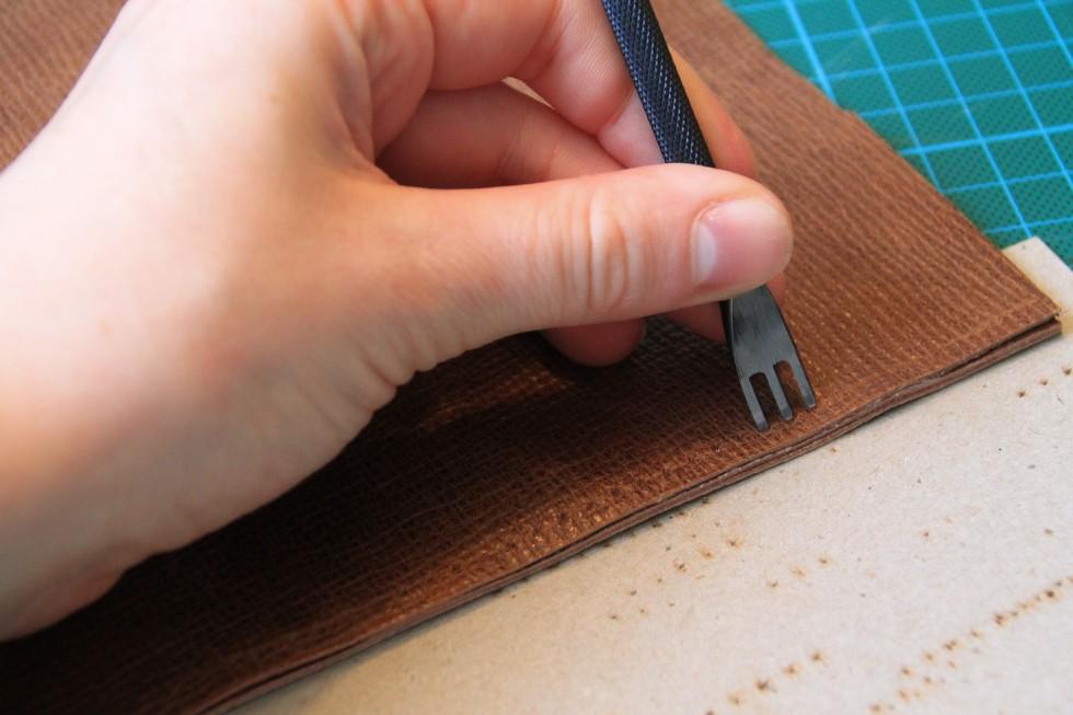 """Når sømrummet er opmærket, skal der laves huller til der, hvor nålen skal stikkes igennem. Til det kan enten bruge en """"diamond hole punch"""" (jeg ved faktisk ikke, hvad de hedder på dansk) eller en syle. På billedet ses førstnævnte."""