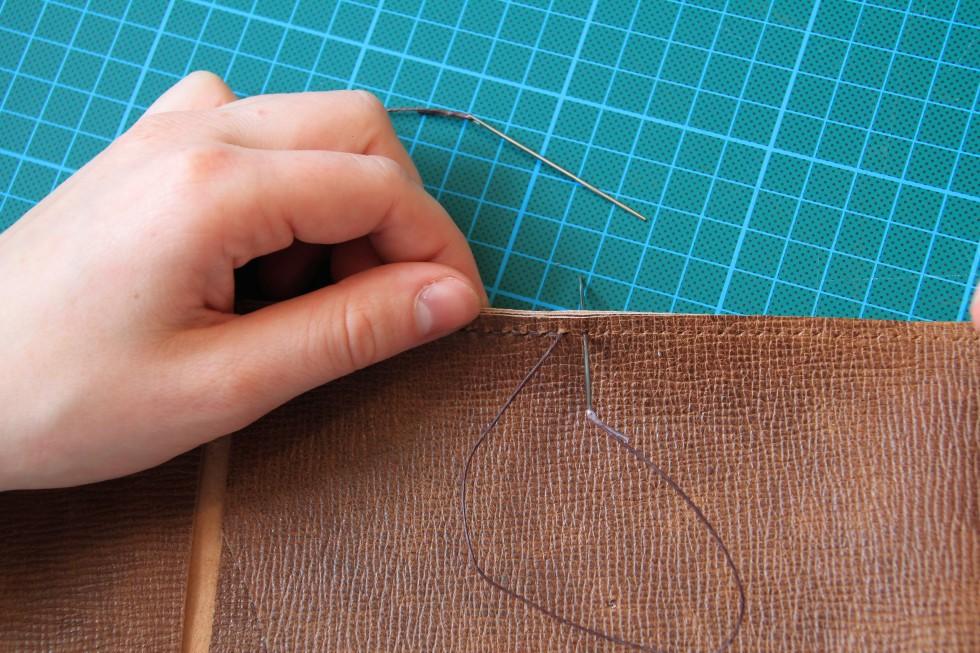 Selve syningen er ikke svær. Alfa omega er, at man har lavet nogle gode huller. Tråden, der skal bruges, skal være vokset - enten kan man selv gøre dette, ellers findes der også butikker, hvor tråden allerede indeholder voks. Der skal sættes en nål på i hver ende af tråden. Trådning af nålene foregår ved, at man først stikker tråden gennem hullet og trækker den ca. 5-7 cm ind. Herefter stikker man spidsen af nålen gennem tråden 1-2 cm fra trådenden og strammer til, så de 1-2 cm fra trådenden nu sidder på den bageste del af nålen. Det samme gøres i den anden ende af tråden med den anden nål. Når man skal til at sy, stikker man den ene nål gennem det første hul, således at der er lige meget tråd på hver sin side af hullet. Nu skal man fra hver sin side stikke først den ene nål og derefter den anden nål igennem og stramme til. Dette gøres hele vejen ned. Dette kaldes sadelmagersyning. Se dette og de efterfølgende to billeder.