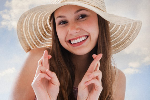 Woman wearing a straw hat and crossing her fingers --- Image by ゥ Mike Kemp/Tetra Images/Corbis